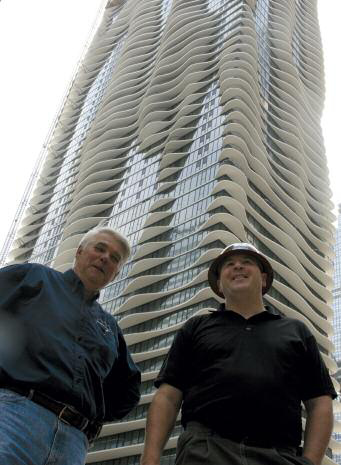 OPP general manager Jim Zmudka (right) with building contractor at the Aqua Tower in Chicago. A major component of construction was OPP's barrier film overlaid panels, specially designed for high alkaline and abrasive concrete applications